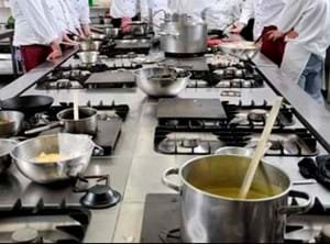 pans cooking on a stove top with chefs in the background