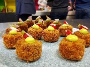 Pork croquette with lovage mayonnaise canape on a table
