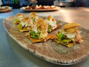 Crab taco charred hispi, chicken skin canape on platter