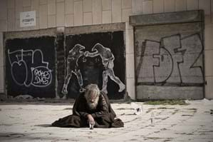 A Begger man sat on the floor in front of a wall of graffiti