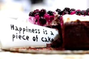 Happiness is a piece of cake saying on a knife cutting a blackberry cake