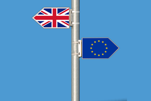 Sign post with EU flag facing one way and UK flag facing another