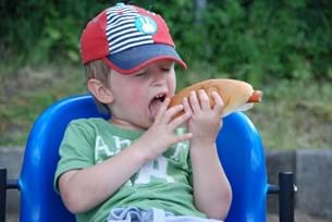 Kid in sun hat eating a hot dog