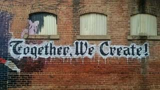 Together we create saying in graffiti on a wall