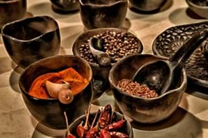 various spices in black bowls with small scoops