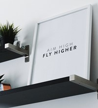 Aim high fly higher saying on a whiteboard on a shelf