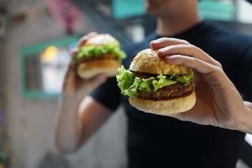 person holding a burger in a bun with lettuce