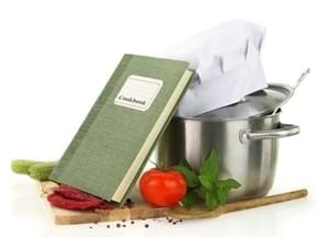 Chopping board with cook book, pan and chef hat on top